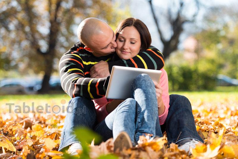 Para ludzi z tabletem w parku